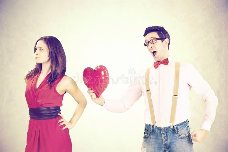 Frau, die das rote Herz ihres Freundes an einem lustigen Valentinsgruß ` s Tag zurückweist lizenzfreies stockfoto