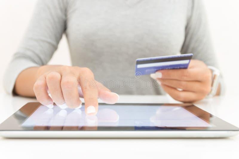 Frau, die das Tabletten- und Kreditkartelohneinkaufen verwendet stockfoto