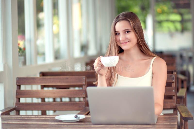 Frau, die das Trinken eines Kaffees oder des Tees bei der Anwendung des Laptops hält stockbild