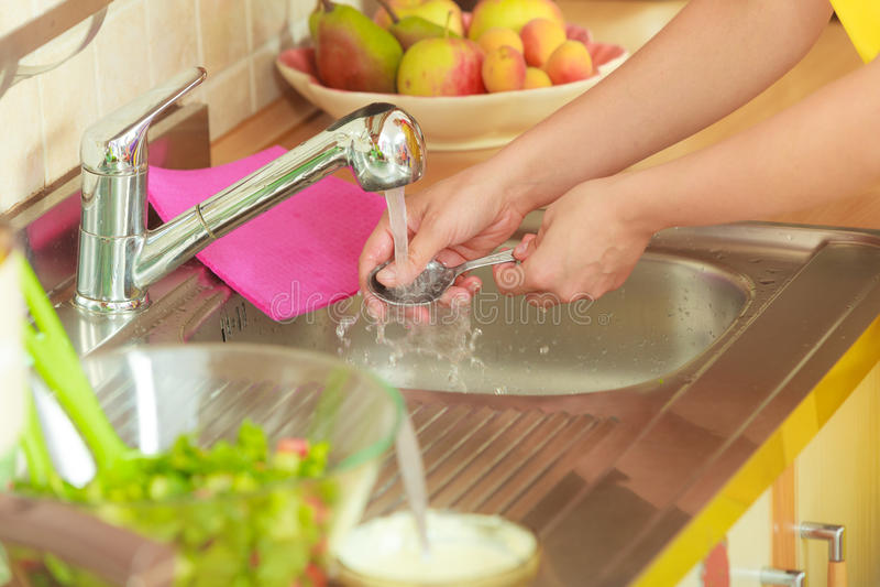 Frau, die das Waschen oben in der Küche tut lizenzfreies stockbild