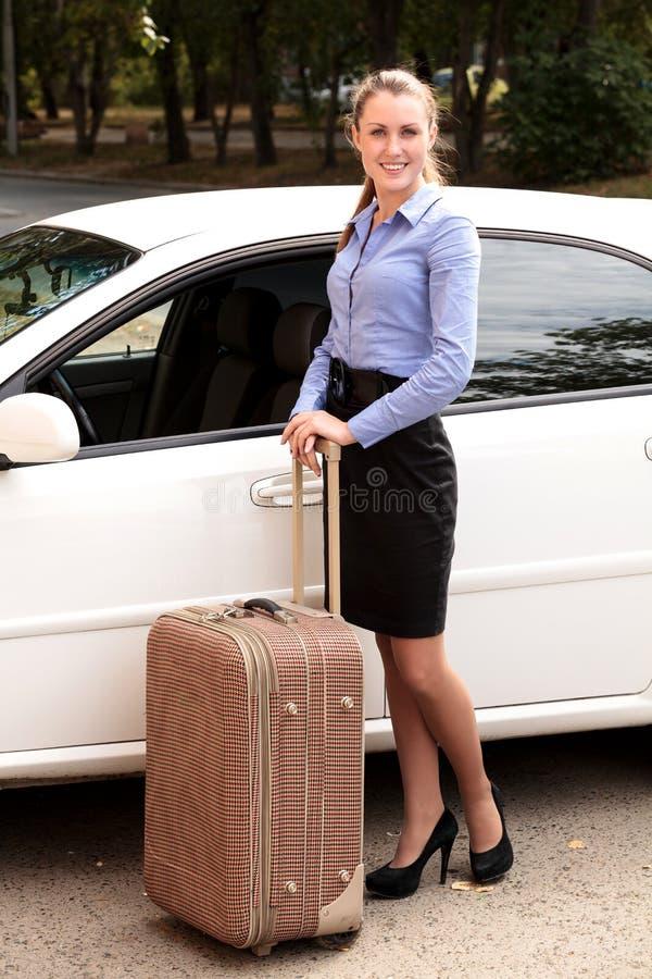Frau, die das weiße Auto mit großem Koffer bereitsteht stockbilder