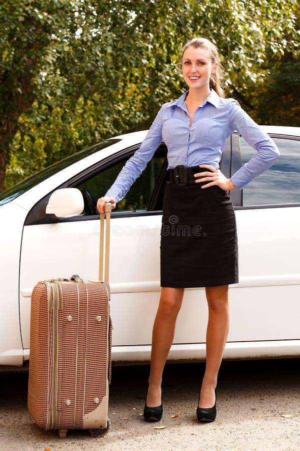 Frau, die das weiße Auto mit großem Koffer bereitsteht lizenzfreies stockbild