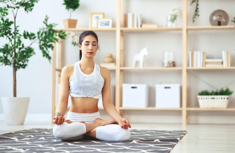 Frau, die das Yoga, zu Hause meditierend in Lotussitz tut stockfotos
