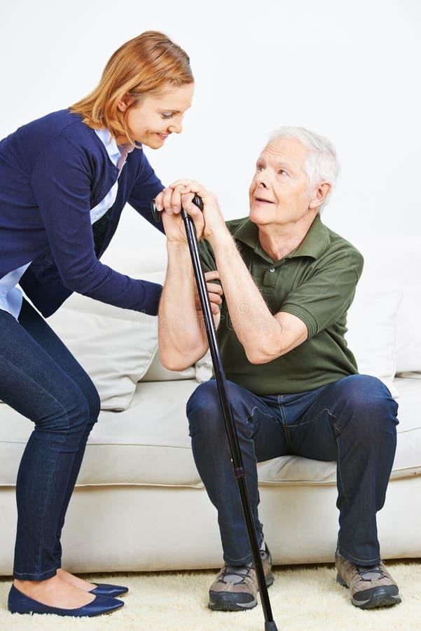 Frau, die dem älteren aufstehenden Mann hilft lizenzfreie stockbilder