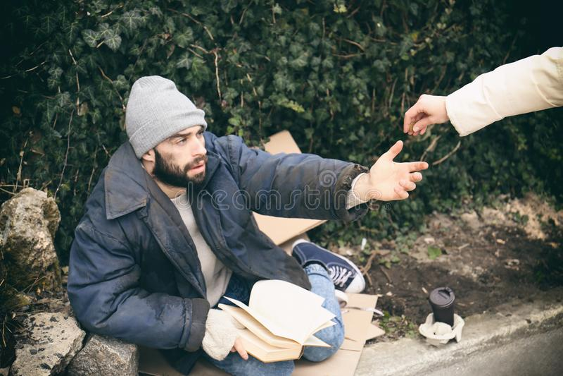 Frau, die dem armen obdachlosen Mann Almosen gibt lizenzfreies stockfoto