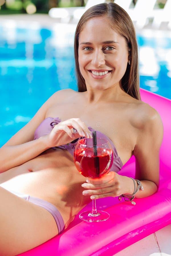 Frau, die dem entspannten Lügen auf Luftmatraze glaubt und Cocktail trinkt stockfotos