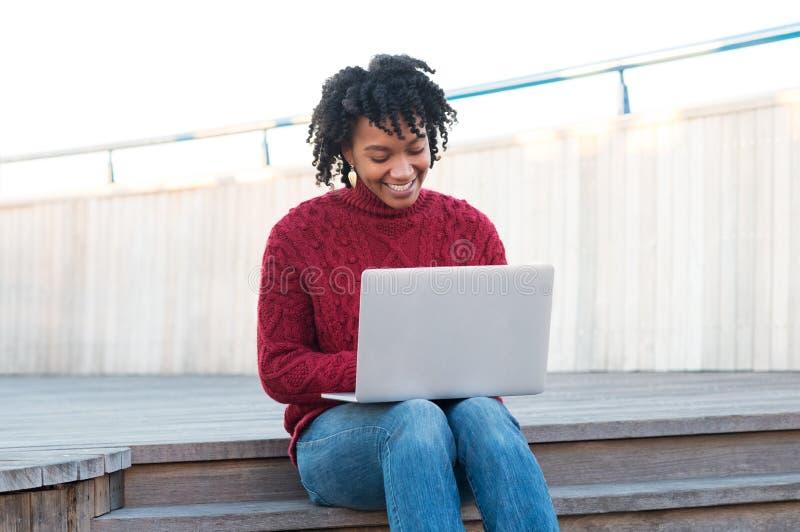 Frau, die an dem Laptop im Freien arbeitet lizenzfreie stockfotos