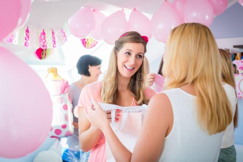 Frau, die dem schwangeren Freund auf Babyparty Geschenk gibt lizenzfreies stockbild