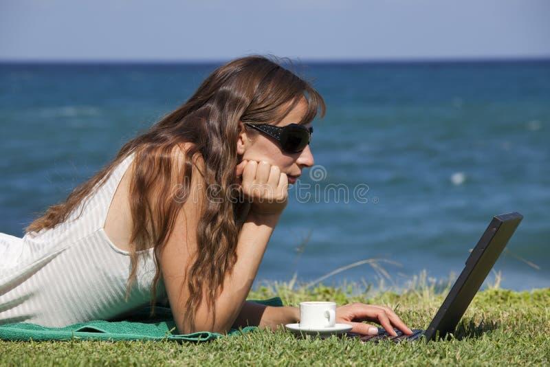Frau, die an dem Strand arbeitet stockbilder