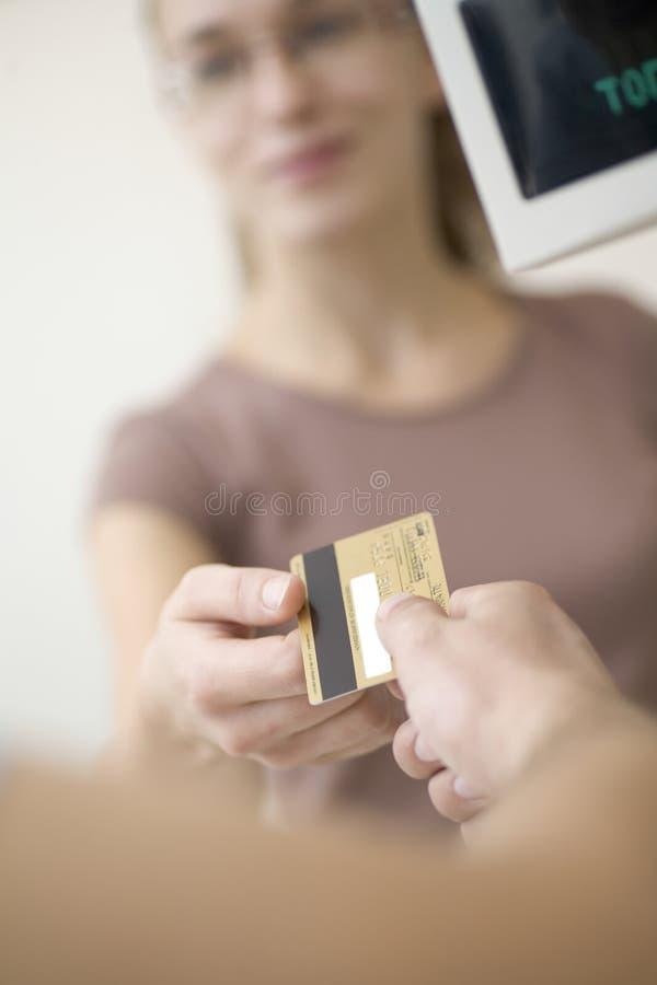 Frau, die dem Verkäufer über eine Kreditkarte überschreitet lizenzfreie stockfotografie
