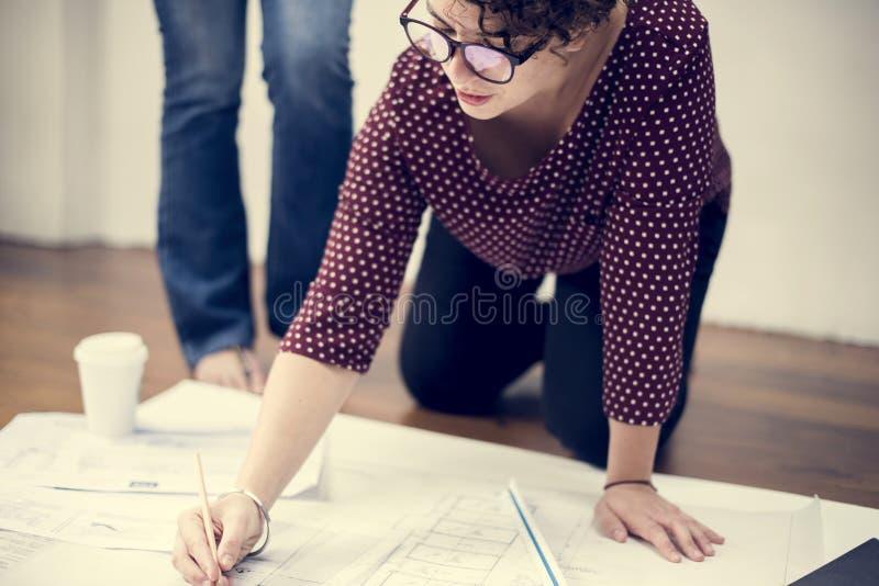 Frau, die an dem Zeichnen eines Planes arbeitet stockbild