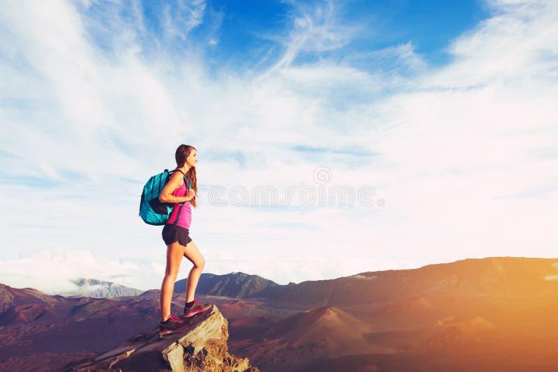 Frau, die in den Bergen bei Sonnenuntergang wandert stockfoto