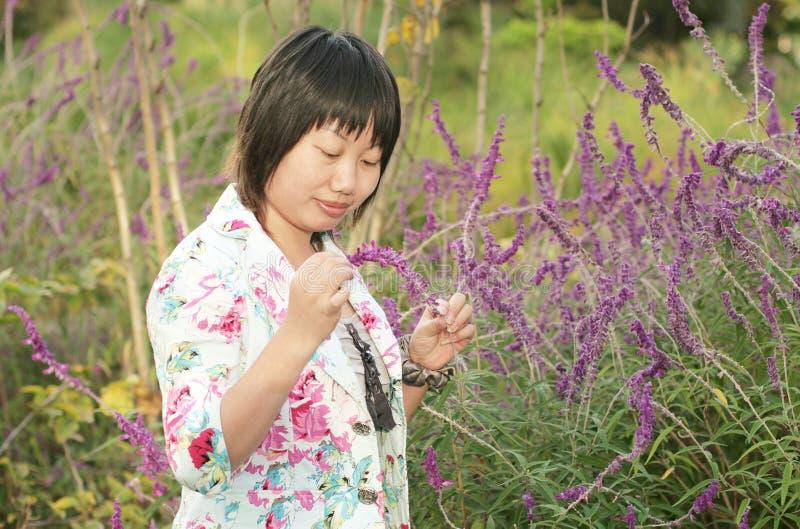 Frau, die an den Blumen lokking ist lizenzfreie stockfotos