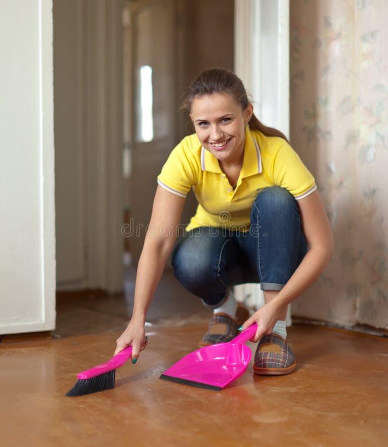 Frau, die den Fußboden fegt stockbild