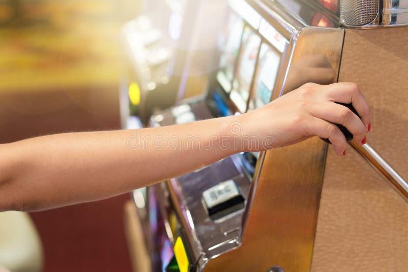 Frau, die den Griff auf einem Spielautomaten in einem Kasino zieht lizenzfreie stockfotografie