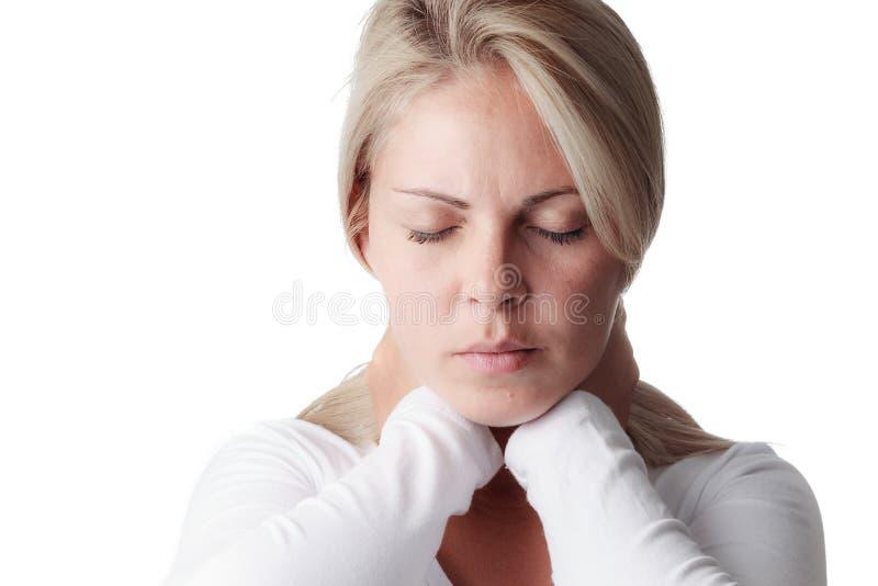 Frau, die den Hals lokalisiert auf weißem Hintergrund hält stockfotografie