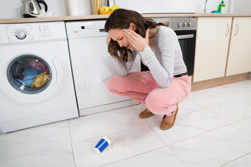 Frau, die den Jogurt gefallen auf den Boden betrachtet lizenzfreie stockbilder