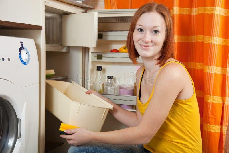 Frau, die den Kühlraum entfrostet stockfotografie