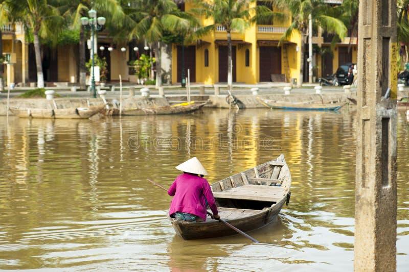 Frau, die den konischen Hut rudert das Boot bei Hoi An trägt lizenzfreies stockfoto