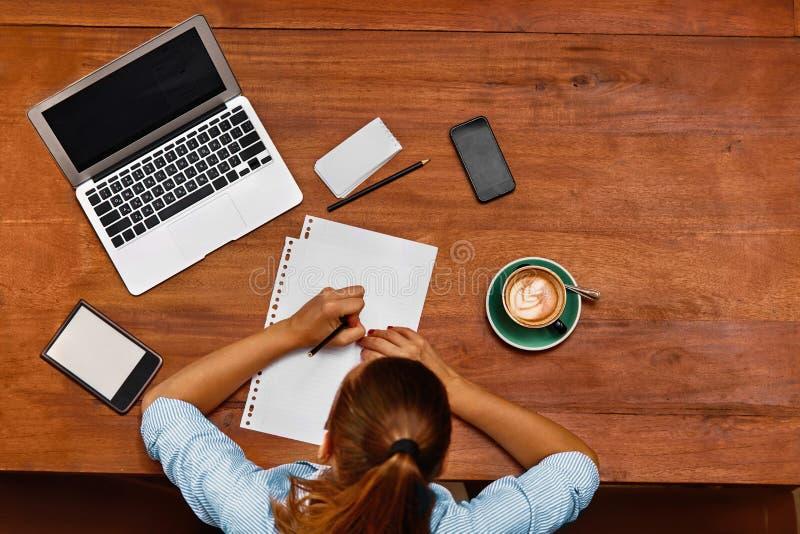 Frau, die den Notebook, Kenntnisse nehmend am Café verwendet funktion lizenzfreies stockbild
