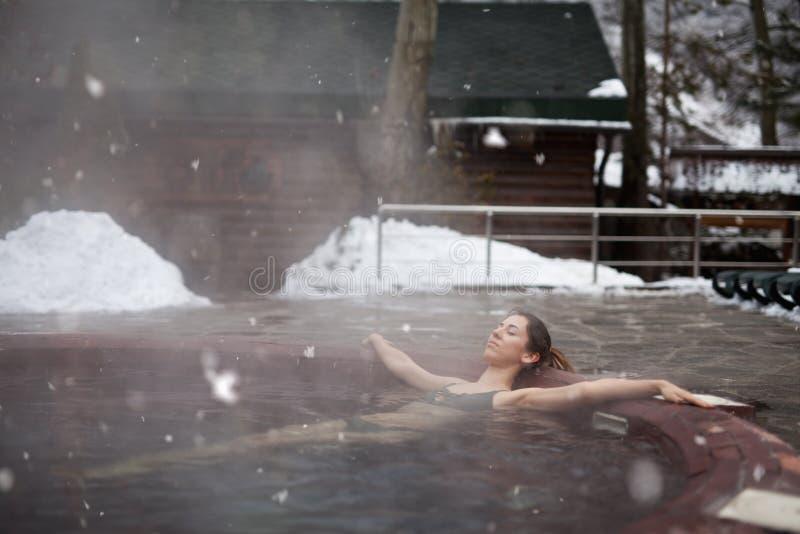 Frau, die den Panoramablick vom Pool in den Alpen genießt lizenzfreie stockfotografie