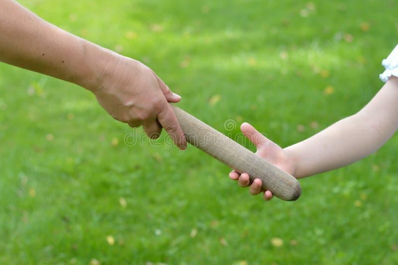 Frau, die den Relaistaktstock in eine Kind-` s Hand gibt stockbild