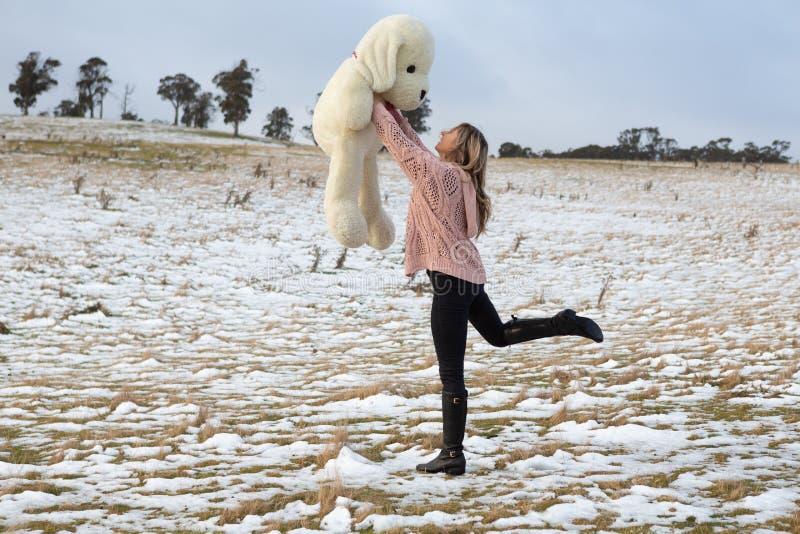Frau, die in den Schnee mit Teddybären scherzt stockfotos