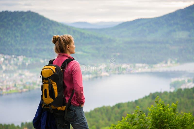 Frau, die den See vom Rand der Klippe betrachtet stockbild
