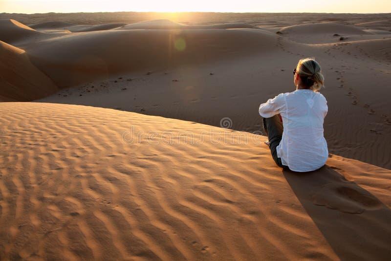 Frau, die den Sonnenuntergang auf den roten Sanddünen von Oman aufpasst lizenzfreie stockfotos