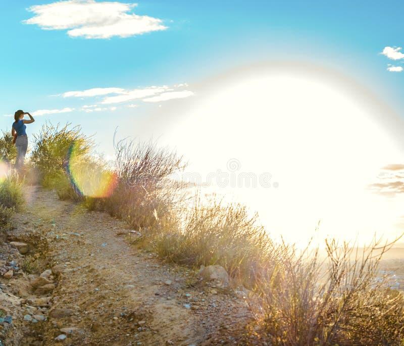 Frau, die den Sonnenuntergang von der Spitze eines Berges betrachtet stockfoto