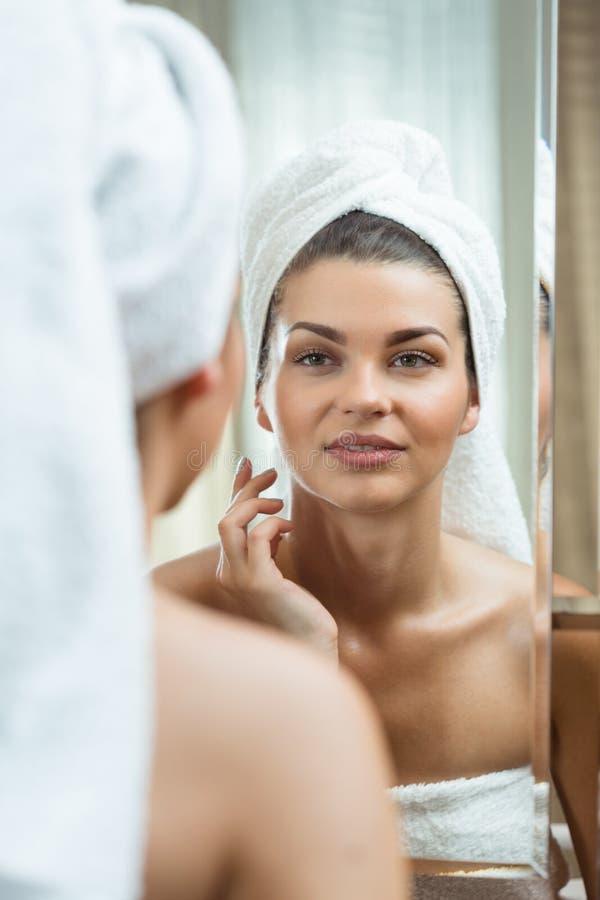 Frau, die den Spiegel betrachtet stockfoto
