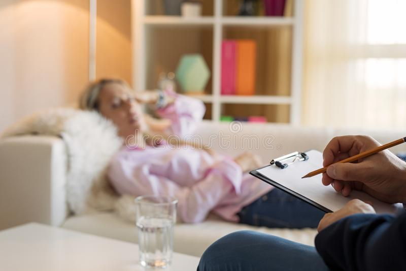 Frau, die in der Couch während hypnotherapy liegt lizenzfreie stockfotos