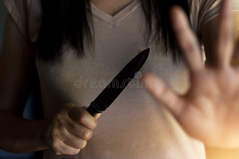 Frau, die in der Hand ein Messer bei der Verteidigung hält stockfoto