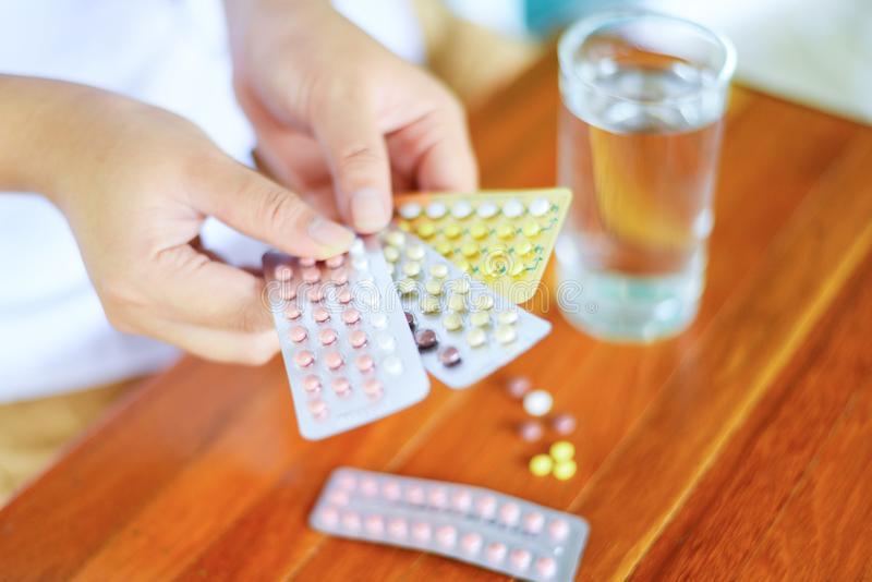 Frau, die in der Hand Empfängnisverhütungspillen - Geburtenkontrolleempfängnisverhütendes mittel hält, hormonale Antibabypillen d lizenzfreies stockbild
