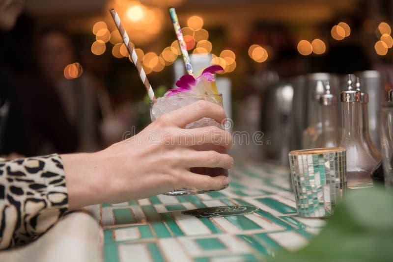 Frau, die in der Hand mojito Cocktail vom Barzähler im Nachtklub hält stockfotos