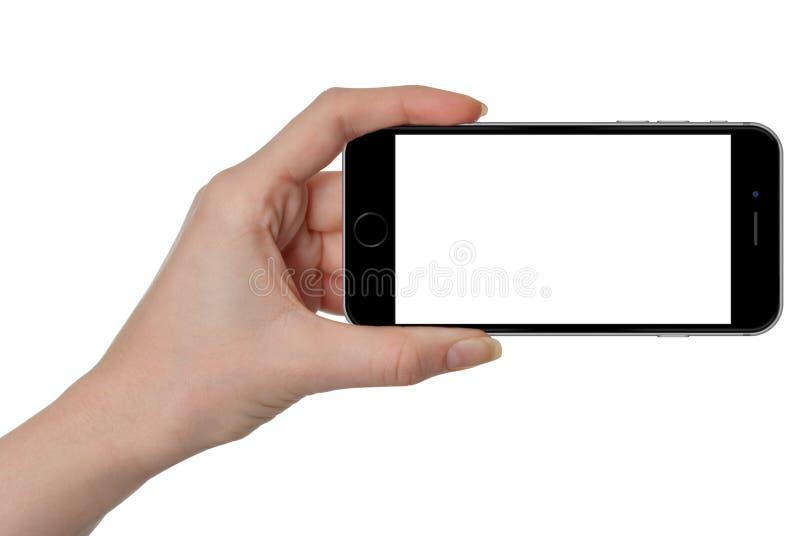 Frau, die in der Hand schwarzes intelligentes Telefon mit lokalisiertem Schirm hält lizenzfreies stockbild