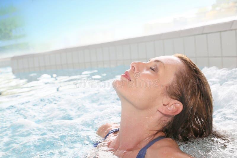 Frau, die in der heißen Wanne nach einem langen Arbeitstag sich entspannt lizenzfreies stockbild