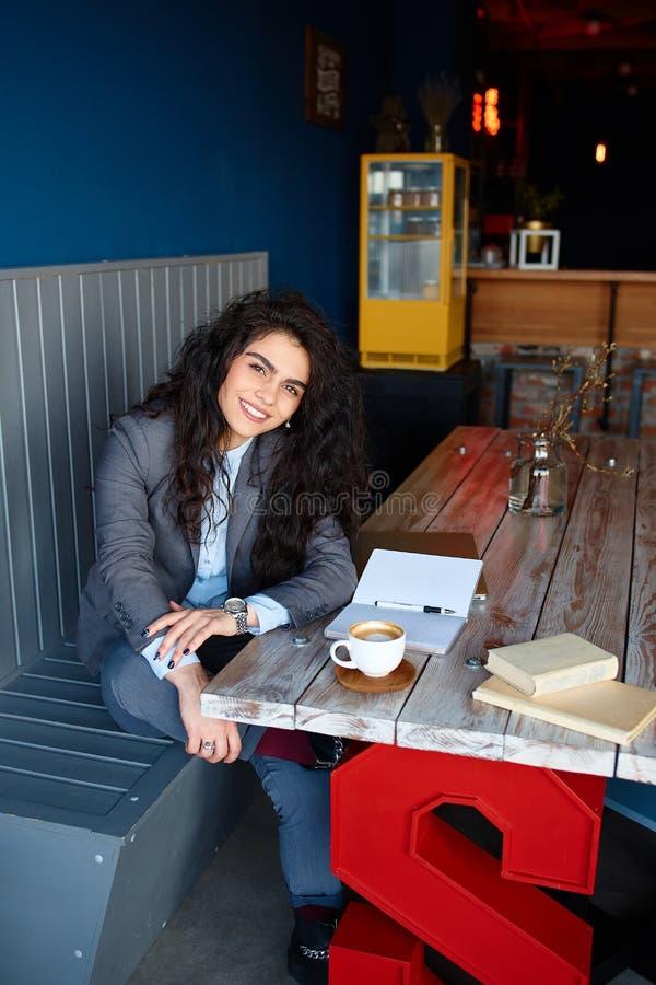 Frau, die in der Kaffeestube sitzt und Anmerkungen schreibt lizenzfreie stockfotografie
