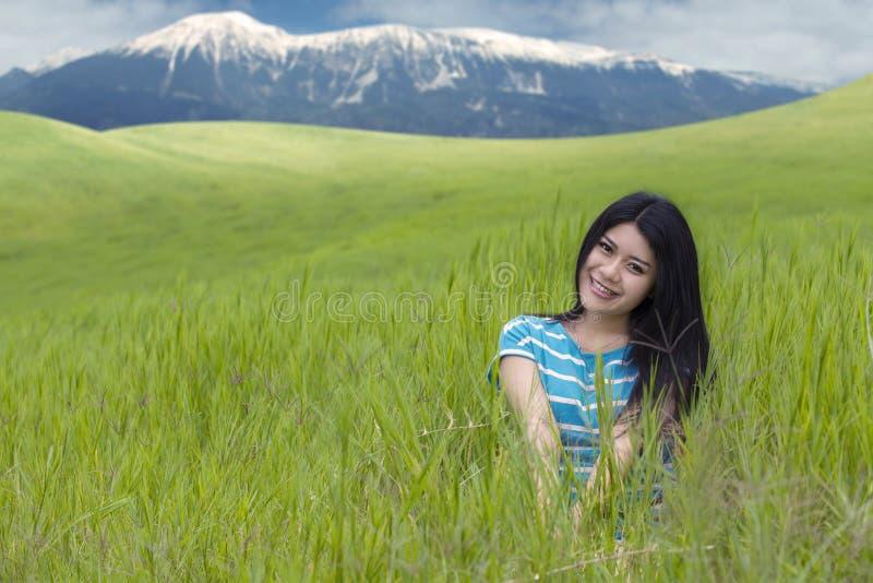 Frau, die an der Kamera mit Bergblick lächelt lizenzfreies stockbild