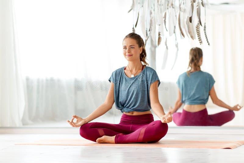 Frau, die in der Lotoshaltung am Yogastudio meditiert lizenzfreie stockfotos
