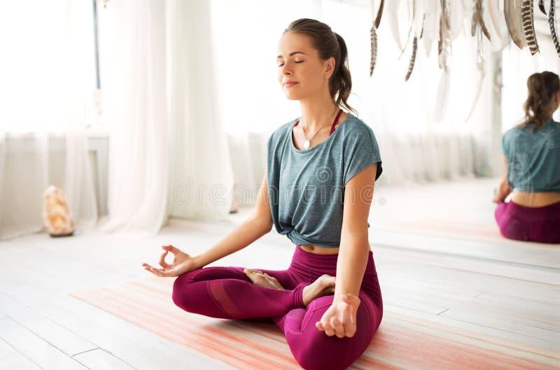 Frau, die in der Lotoshaltung am Yogastudio meditiert stockbild