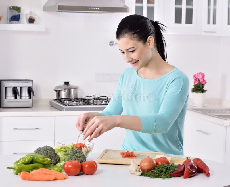 Frau, die in der neuen Küche bildet gesunde Nahrung mit Gemüse kocht lizenzfreie stockbilder