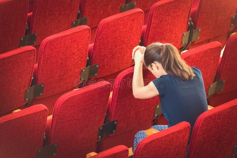 Frau, die in der Reihe von den betenden Stühlen sitzt lizenzfreie stockbilder