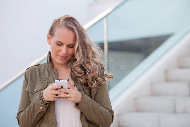 Frau, die an der Zelle oder am Handy simst stockbild