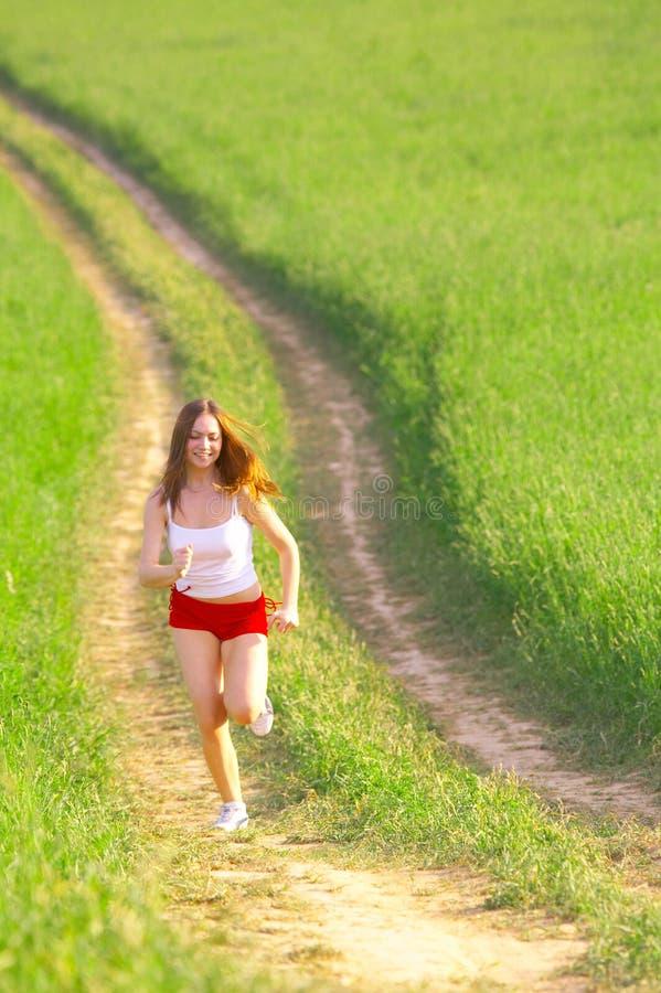 Frau, die in die Felder läuft stockfotos