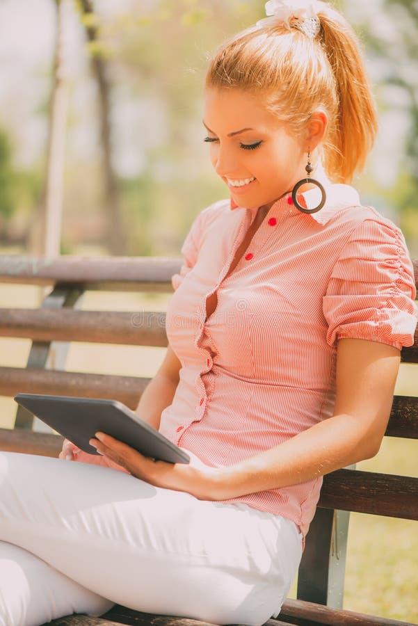 Frau, die digitale Tablette im Park verwendet stockbild