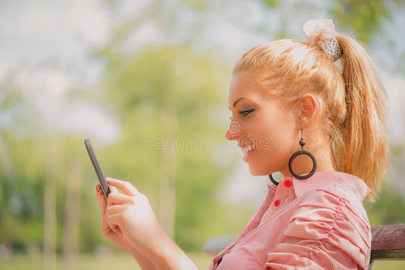 Frau, die digitale Tablette im Park verwendet stockbilder