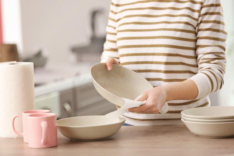 Frau, die Dishware mit Papierhandtuch abwischt lizenzfreie stockfotografie