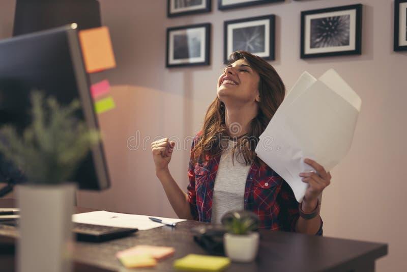 Frau, die Dokumente froh nach Geschäftserfolg verwahrt stockfotos