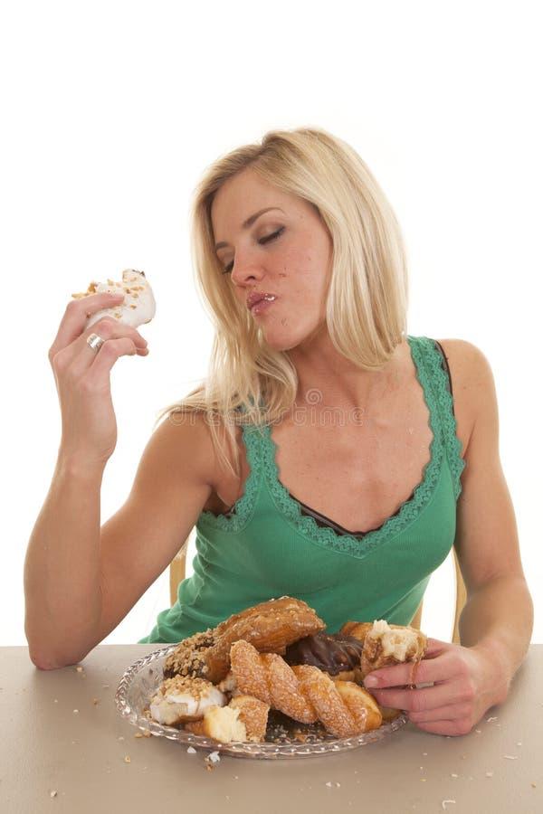 Frau, die Donuts genießt lizenzfreie stockfotos